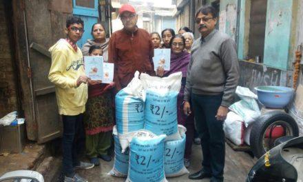 नीले कार्ड धारकों को राशन वितरित करते हुए साथ है भाजपा नेता अनिल जैन।